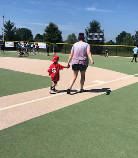 mom and child walk on baseball field
